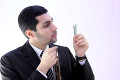 Arab business man praying for help. Image of arab business man wearing black suit and holding rosary asking god for help and looking at money Stock Photo