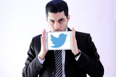 Arab business man with twitter. Image of arab business man wearing black suit and holding white tablet with twitter display stock images