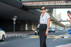 Arab business and success. Confident arabic businesswoman. Standing in the street in formal attire. Businessman standing near skyscrapers in Dubai downtown in Royalty Free Stock Image