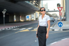 Arab business and success. Confident arabic businesswoman. Standing in the street in formal attire. Businessman standing near skyscrapers in Dubai downtown Royalty Free Stock Photography