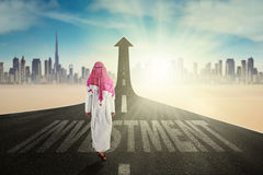 Arab businessman with arrow and Investment word Royalty Free Stock Image