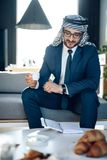 Arab businessman with coffe and notebook on couch at hotel room. royalty free stock images
