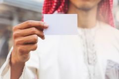 Arab Businessman hand showing business card. In city Stock Photo