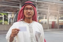 Arab Businessman hand showing business card. In city Royalty Free Stock Photos