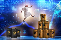 The arab businessman jumping from oil barrels Royalty Free Stock Photos