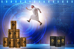 The arab businessman jumping from oil barrels Stock Photo
