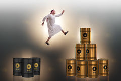 The arab businessman jumping from oil barrels Royalty Free Stock Photo