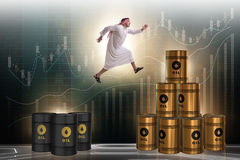 The arab businessman jumping from oil barrels Stock Photos