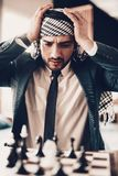 Arab businessman playing chess and grabbed head. Arab Businessman. Man Wearing in Black Suit. Experienced Entrepreneur. Successful Young Man. portrait of Arab royalty free stock photos