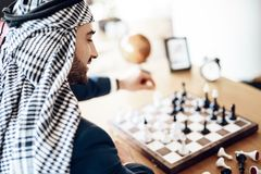 Arab businessman playing chess at table at hotel room. stock photo