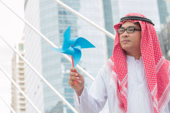 Arab businessman playing with paper windmills Stock Photos