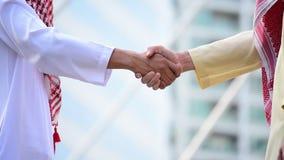 Arab Businessman shaking hands together. Teamwork business partner wear Muslim dress Shake Hands with Partnership Concept. Success