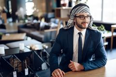 Arab businessman sitting at the table at hotel room. Bearded arab businessman in suit sitting at the table at hotel room royalty free stock image