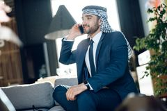 Arab businessman speaking on phone on couch at hotel. Bearded arab businessman in suit speaking on phone on couch at hotel Stock Photo