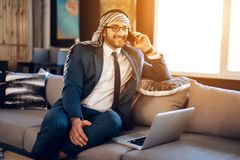 Arab businessman speaking on phone on couch at hotel room. Bearded arab businessman in suit speaking on phone on couch at hotel room Stock Photo