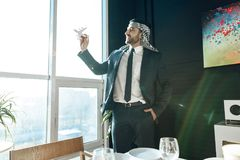 Arab businessman standing at window with model airplane. Royalty Free Stock Image