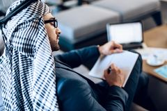 Arab businessman taking notes on couch at office room. Bearded arab businessman in suit taking notes on couch at office room stock image