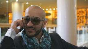 Arab businessman talking on mobile phone. At a shopping center stock video