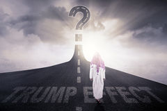 Arab businessman with Trump Effect word on road. Back view of Arabian businessman walking on the highway with a question mark and text of Trump Effect on the Stock Photos