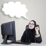 Arab businesswoman with empty bubble. Image of Arabian woman sitting in front of computer and thinking of new ideas with empty bubble Stock Photography