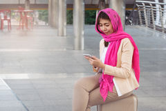 Arab businesswoman messaging on a mobile phone in the city. Woman Royalty Free Stock Images