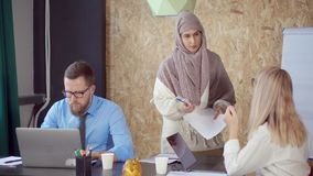 Arab and caucasian woman are discussing and taking paper in modern office stock footage