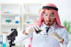 The arab chemist scientist testing quality of oil petrol. Arab chemist scientist testing quality of oil petrol stock photography