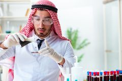 The arab chemist scientist testing quality of oil petrol. Arab chemist scientist testing quality of oil petrol stock photo