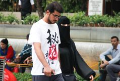 Arab couple: a young man with glasses and a beard is walking with a woman dressed in a black burka royalty free stock photo