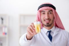 The arab dentist working on new teeth implant. Arab dentist working on new teeth implant stock photo