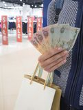 Arab dirhams in a woman`s hand on the background of sales in the store. Shopping bags in a woman`s hand. Arab dirhams in a woman`s hand on the background of stock images