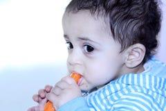 Arab egyptian baby girl eating carrot Stock Photo