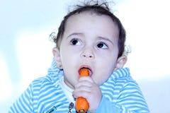 Arab egyptian baby girl eating carrot Royalty Free Stock Photo