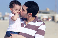 Arab egyptian father kissing his daughter. Photo of arabian father kissing his little daughter on sand going to beach in egypt Stock Photo