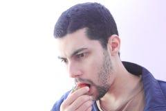 Arab egyptian guy eating strawberry Royalty Free Stock Photos