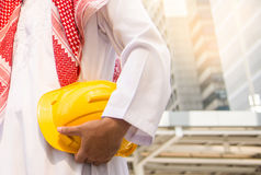 Arab Engineer or Safety officer holding helmet construction or yellow helmet for workers security. Royalty Free Stock Photography