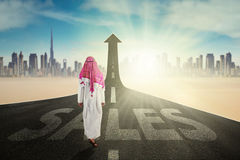 Arab entrepreneur with arrow and Sales word Stock Image