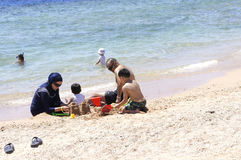 SHARM EL SHEIKH, EGYPT - MAY 8, 2014: Egyptian family on the beach sculpts figures out of the sand Royalty Free Stock Image