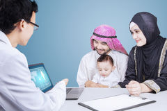 Arab family and pediatrician looking at a laptop Stock Photography