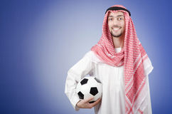 Arab with football in studio shooting. On blue Royalty Free Stock Photos