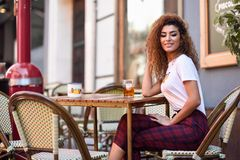 Arab girl in casual clothes drinking a soda in an outdoors bar royalty free stock photo
