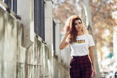 Arab girl in casual clothes in the street. Beautiful young arabic woman with black curly hairstyle. Arab girl in casual clothes in the street. Happy female Royalty Free Stock Images