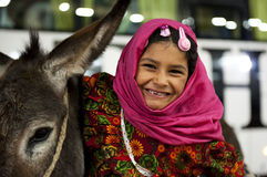Arab girl pulling a donkey and looking at photographer with a smile Royalty Free Stock Photo
