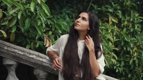 Alone arabian woman is standing in a tropical garden and touching her long hair stock video