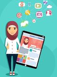 Arab girl with tablet computer. The concept of social networking. Arab girl with tablet computer showing a social network. Personal page of a social network Royalty Free Stock Images
