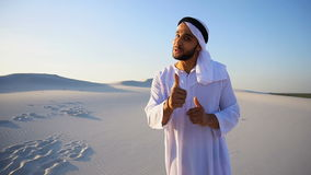 Arab guy advertising agent looking at camera tells information and shakes handshake, standing in middle of wide desert. Portrait of Muslim Arabian Sheikh  male stock video