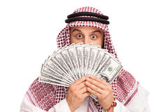 Arab hiding behind a stack of money. Young Arab hiding his face behind a stack of money isolated on white background Stock Photo