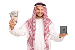 Arab holding money and a small metal safe Stock Photo