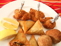Arab kubbe samosas and chicken wings. A plate of Arabian kubbe (meatballs), breaded and fried chicken wings,  and samosa pastries which are commonly served as Royalty Free Stock Photos