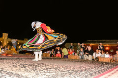 Arab male dancer performing in front of a crowd in Arabian deser Stock Photos